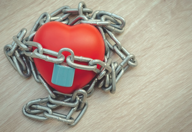 Padlock and chain locking a red heart on the wooden floor.