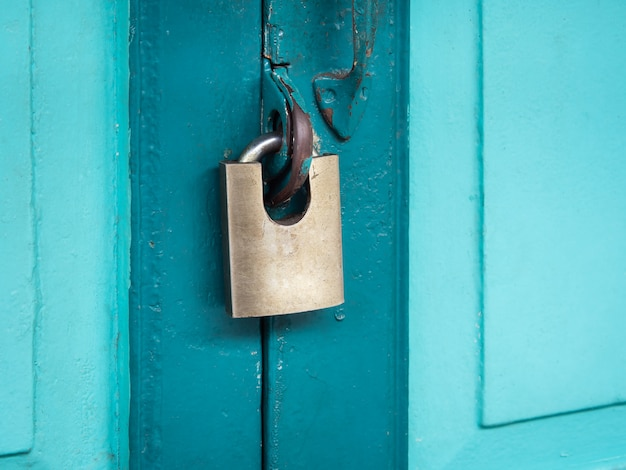 Padlock hanging on emerald green  wooden door