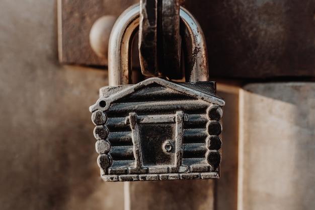 Замок на замке в виде хижины висит на петлях закрытых ворот. металлические ворота.