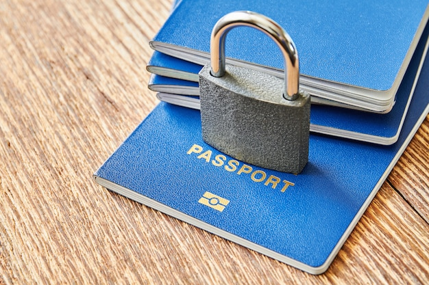 A padlock and passports on the wooden surface. coronavirus and travel concept. closing borders between countries due to virus. closeup