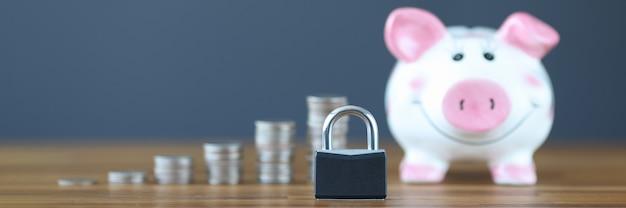 Замок, стоящий на фоне копилки и монет крупным планом, безопасное хранение концепции средств