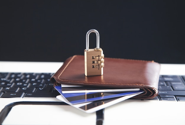 Padlock, wallet and credit cards on the computer keyboard. credit card security