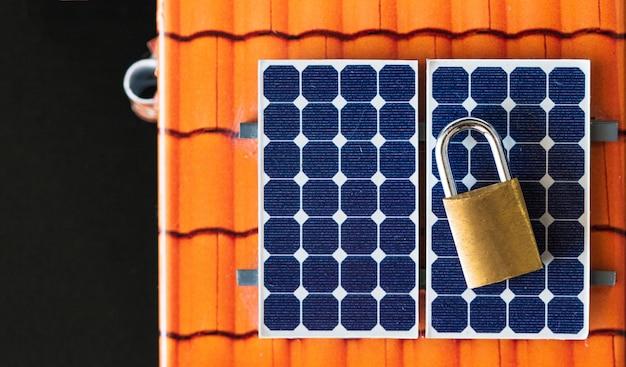Padlock with key on photovoltaic solar panel on black