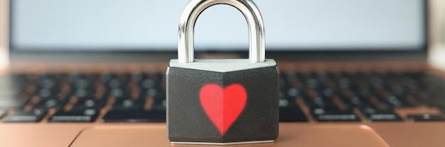 Замок с окрашенным красным сердцем, стоящий на клавиатуре ноутбука крупным планом