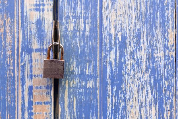 Замок на синем фоне деревянной стены.