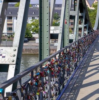 Замки на мосту во франкфурте-на-майне, германия. ритуал прикрепления замков к мосту как символа любви был распространен в европе с 2000-х годов.