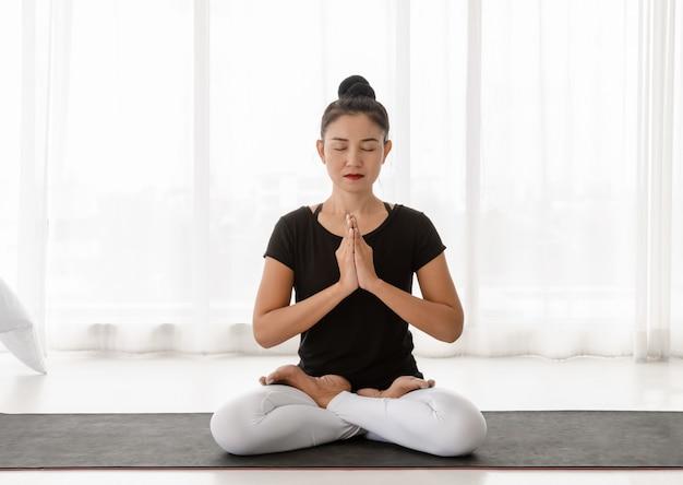 ロータスポーズまたは白い寝室で上げられた手ナマステでpadmasanaに座って、自宅でヨガの瞑想の練習をしているアジアの女性。