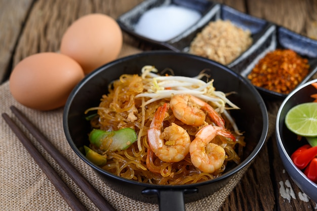 Padthai shrimp in a black bowl with eggs and seasoning on wooden table.