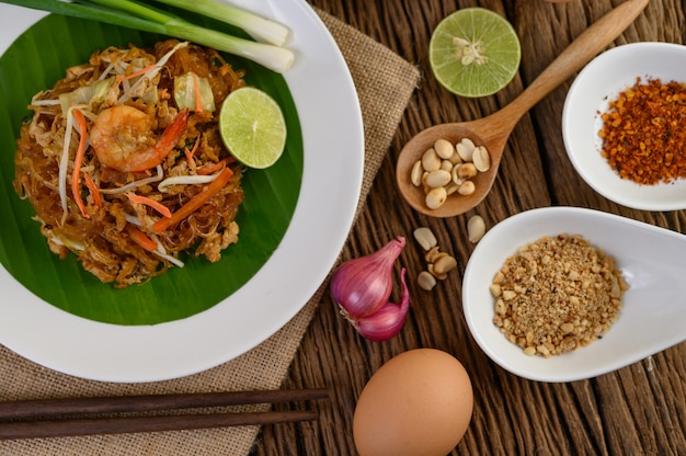 Padthai shrimp in a black bowl with eggs, spring onion, and seasoning on wooden table.