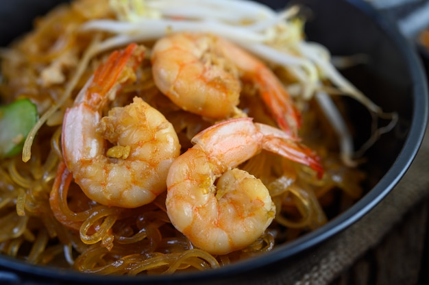 Padthai shrimp in a black bowl.