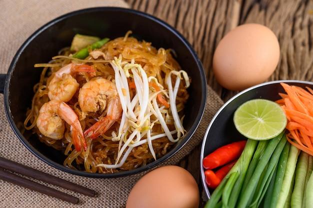 卵と木製のテーブルの調味料と黒のボウルにパタイエビ。