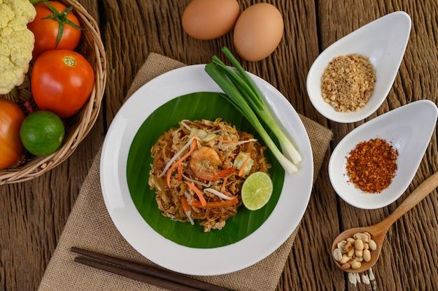 卵、ネギ、および木製のテーブルの調味料と黒のボウルにパタイエビ。