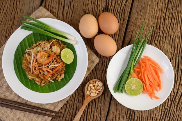 ライムと木製のテーブルに卵と白い皿のパタイシュリンプ。