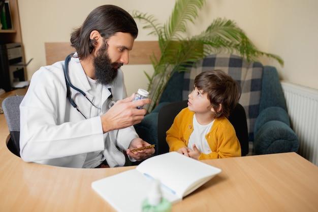 Врач-педиатр осматривает ребенка в комфортном медицинском кабинете. здравоохранение, детство, медицина, концепция защиты и профилактики. маленький мальчик доверяет врачу и испытывает спокойствие, положительные эмоции.