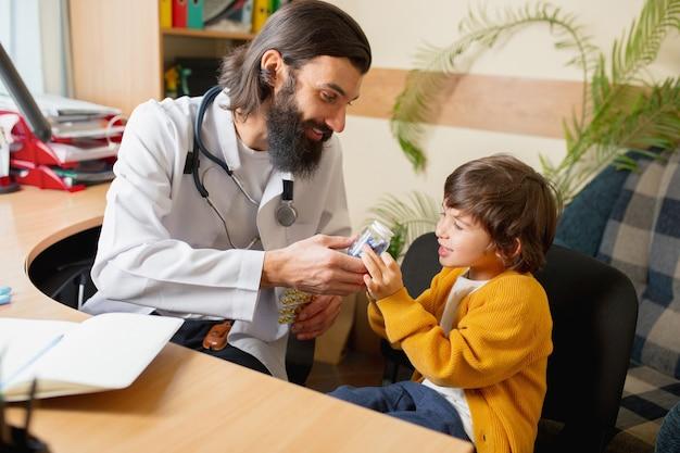 Comfortabe診療所で子供を診察する小児科医。ヘルスケア、小児期、医学、保護および予防の概念。小さな男の子は医者に信頼し、穏やかで前向きな感情を感じます。