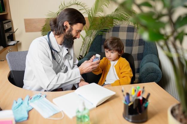 Medico pediatra che esamina un bambino in uno studio medico confortevole. concetto di assistenza sanitaria, infanzia, medicina, protezione e prevenzione. il ragazzino si fida del medico e si sente calmo, emozioni positive.