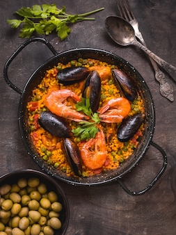 Paella in black pan with rice, shrimps, mussels, squid and meat, bowl with olives and vintage cutlery.