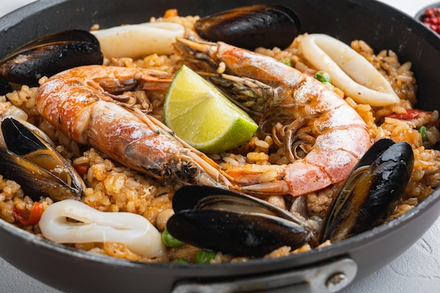 Paella cooked in frying pan on white textured background