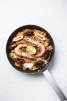 Паэлья, приготовленная в сковороде на белом текстурированном фоне, плоская планировка, фото еды.