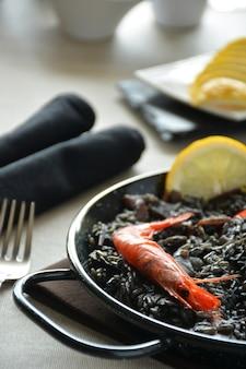 Paella of rice black with squid