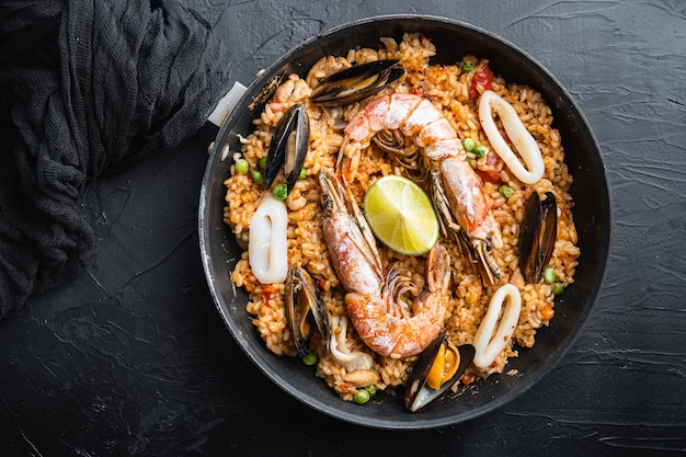 Paella traditional spanish dish served in frying pan, on black textured surface
