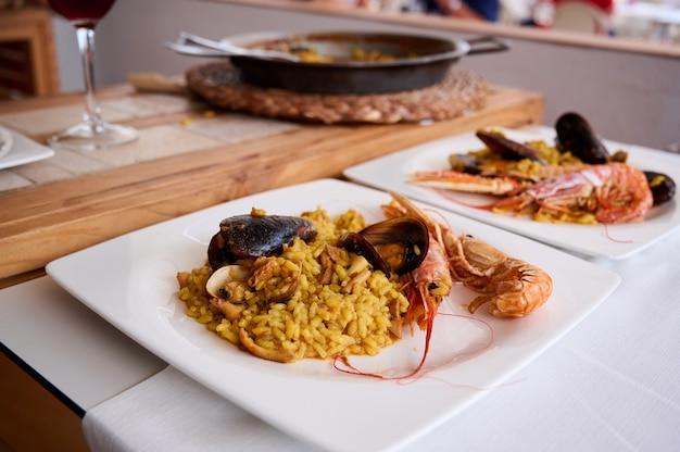 パエリヤ。伝統的なスペイン料理、ムール貝、キングエビ、アカザエビ、イカを添えたフライパンのシーフードパエリア。外でパエリアを調理する