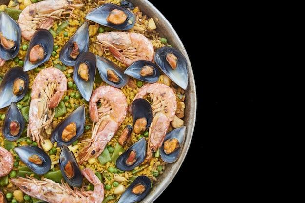 Паэлья, типичная испанская еда, с морепродуктами, овощами, мясом и рисом