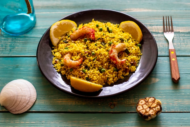 Paella with shrimp on a blue wooden