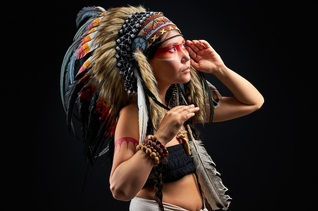 異教の女性は黒い壁のスタジオのシャーマンであり、儀式をしている髪に羽を持つ女性の側面図です