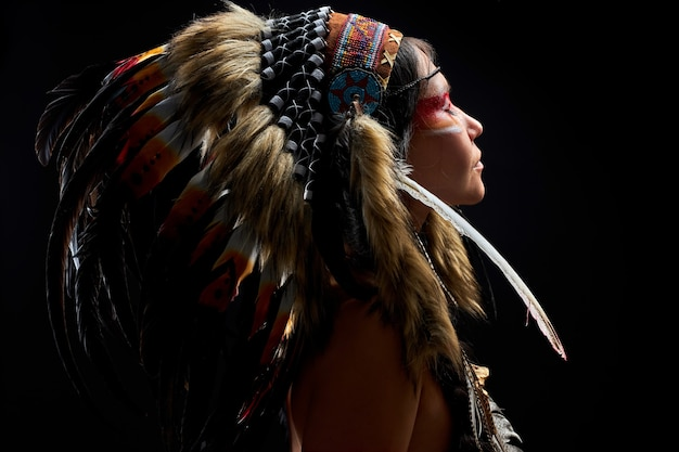 Pagan woman is a shaman in  on black wall, side view on female with feathers on hair doing ritual