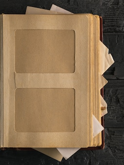 黒い木製のテーブルの上の古い写真アルバムのページ。家族の価値観の主題。上からの眺め。フラットレイ。