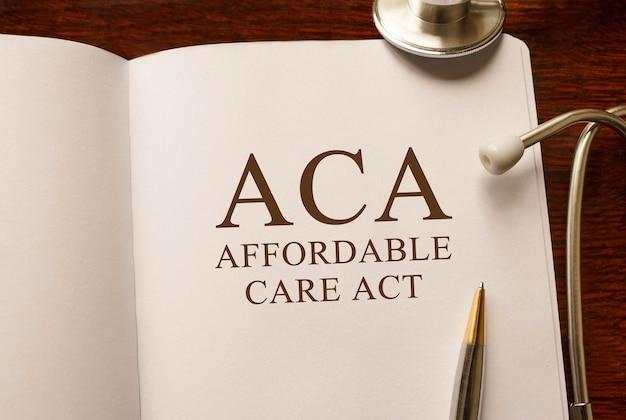 Страница с актом о доступном медицинском обслуживании aca на столе со стетоскопом, медицинская концепция