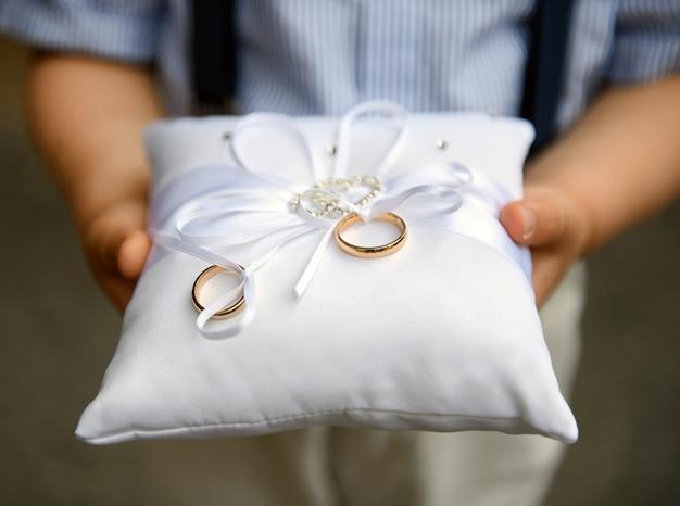 Мальчик-пейдж держит на подушке два золотых обручальных кольца или кольца Premium Фотографии