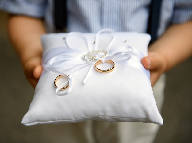 Pageboy holding two gold wedding bands or rings on a cushion Premium Photo