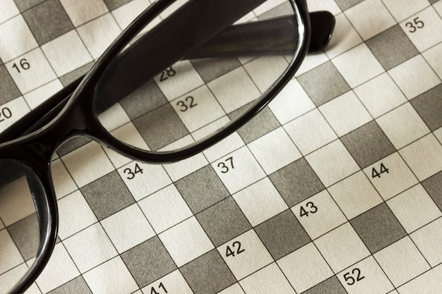 Pages of the magazine with the crossword puzzle and glasses