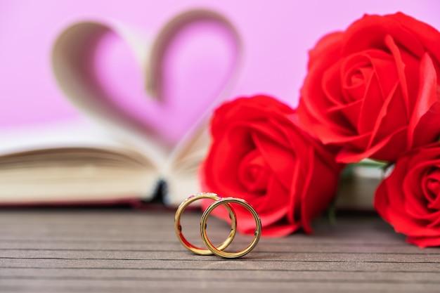 책의 페이지는 붉은 장미와 결혼 반지로 하트 모양으로 구부러져 있습니다. 책 페이지에서 심장 모양의 사랑 개념