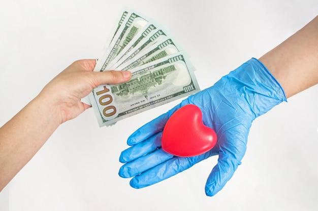 유료 약. 환자의 손은 의사에게 돈을 내밀고 있습니다. 의료 보험 비용. 부패의 개념입니다. 의료 지불 개념입니다.