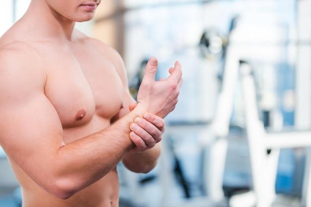トレーニング後の痛み。ジムに立っているときに彼の背中を曲げて触れている筋肉の男のクローズアップ