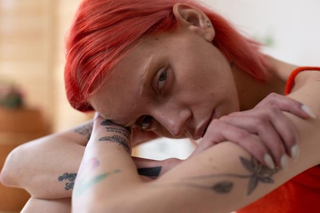 Боль и несчастье. крупным планом рыжеволосая женщина с татуировками чувствует боль и страдание от анорексии