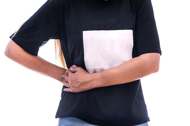 痛みの概念。腹の側の女性の手