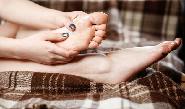 Pain in the foot, girl holds her hands to her feet, foot massage, cramp, muscular spasm, rub the cream into the foot, close-up