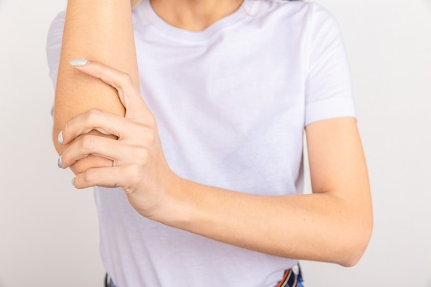 Pain in hand, girl holds her cubit on white. sore elbow joint from inflammation and arthritis.