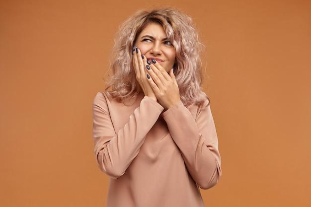 痛み、病気、健康、病気、歯科治療、人々とライフスタイルの概念。彼女の頬に手を置いているボリュームのある髪型を持つ感情的な欲求不満の若い白人女性