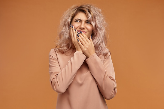 Pain, illness, health, sickness, dental care, people and lifestyle concept. emotional frustrated young caucasian woman with voluminous hairdo putting hand on her cheek