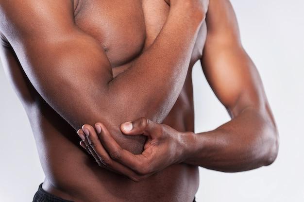 Боль в локте. обрезанное изображение молодого мускулистого африканского мужчины, касающегося его локтя, стоя на сером фоне