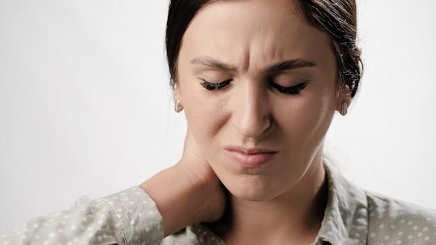 白い背景のクローズアップの首の痛みと首の痛みに苦しんでいる女性の痛み