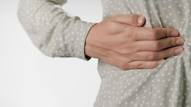 Боль в правом боку, боль в печени, женская рука касается правой стороны живота крупным планом