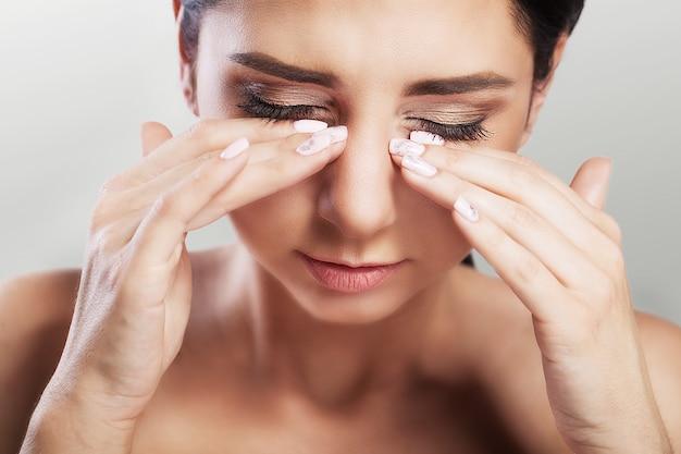 눈에 통증이. 젊은 아름 다운 여자는 그녀의 눈 앞에서 그녀의 손을 보유하고있다. 강한 고통. 건강의 개념.