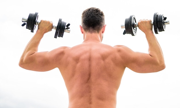 Pain is temporary, pride is forever. sportsman with strong back and arms. sport equipment. bodybuilding sport. dumbbell exercise gym. muscular man exercising with dumbbell rear view. sport lifestyle.