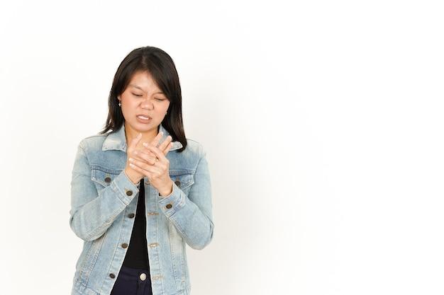 Боль на руке красивой азиатской женщины в джинсовой куртке и черной рубашке, изолированной на белом